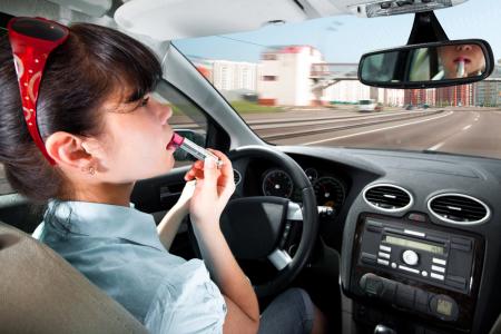 женщина красит губы за рулем
